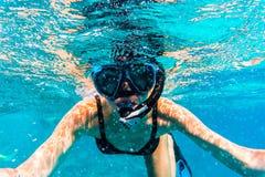 Donna con la maschera che si immerge in chiara acqua di mare immagini stock libere da diritti