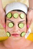 Donna con la mascherina facciale della fetta del cetriolo alla stazione termale fotografie stock libere da diritti