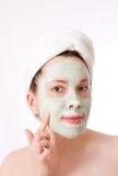 Donna con la mascherina verde sul suo fronte, crema Immagine Stock