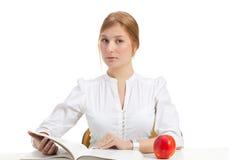 Donna con la mela ed il libro Fotografia Stock