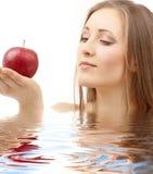 Donna con la mela rossa in acqua immagine stock libera da diritti