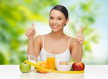 Donna con la misura di nastro e dell'alimento che mostra i pollici su Immagini Stock Libere da Diritti