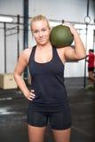 Donna con la palla di colpo al centro della palestra di forma fisica Immagine Stock Libera da Diritti