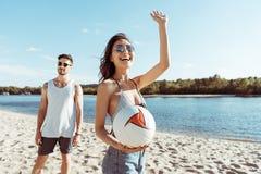 Donna con la palla di pallavolo a disposizione che ondeggia a qualcuno sulla spiaggia Fotografia Stock Libera da Diritti
