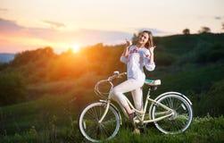 Donna con la retro bici sulla collina nella sera fotografia stock