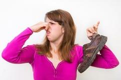 Donna con la scarpa puzzolente del suo marito Immagini Stock