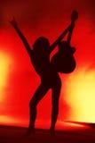 Donna con la siluetta della chitarra su priorità bassa rossa Fotografia Stock Libera da Diritti