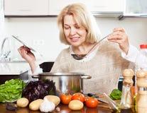 Donna con la siviera che cucina minestra in pentola in cucina domestica Fotografia Stock Libera da Diritti