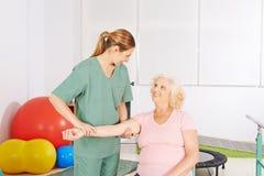 Donna con la spalla facente male nella terapia fisica immagine stock libera da diritti