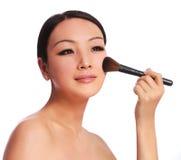 Donna con la spazzola di trucco. la bella applicazione castana asiatica arrossisce sulla sua guancia, isolata Fotografie Stock