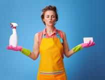 Donna con la spugna della cucina e una bottiglia del detersivo che fa yoga fotografie stock libere da diritti
