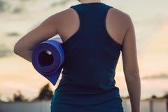 Donna con la stuoia pronta contro al tramonto immagini stock libere da diritti