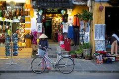 Donna con la sua bicicletta in cappello conico tradizionale sul mercato fotografia stock
