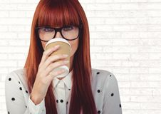 Donna con la tazza di caffè sopra il fronte contro il muro di mattoni bianco Fotografia Stock