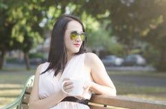 Donna con la tazza di caffè in un parco Immagine Stock Libera da Diritti