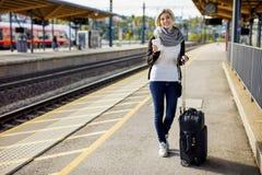 Donna con la tazza di caffè e dei bagagli che aspetta alla stazione ferroviaria Fotografia Stock Libera da Diritti
