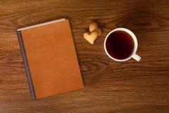 Donna con la tazza di tè, dei biscotti e del libro su legno Fotografie Stock
