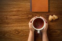 Donna con la tazza di tè, dei biscotti e del libro su legno Fotografie Stock Libere da Diritti