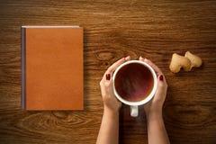 Donna con la tazza di tè, dei biscotti e del libro su legno Fotografia Stock
