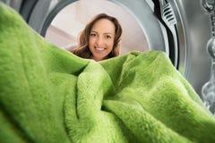 Donna con la vista dell'asciugamano dall'interno della lavatrice Fotografia Stock