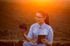 Donna con la zolla della terra e della compressa Immagini Stock Libere da Diritti