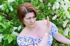 Donna con le allergie nel parco di fioritura della molla Immagini Stock Libere da Diritti