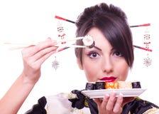 Donna con le bacchette ed i sushi Fotografia Stock