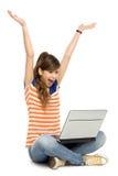 Donna con le braccia alzate per mezzo del computer portatile Fotografie Stock