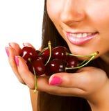 Donna con le ciliege su bianco Immagini Stock
