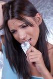 Donna con le compresse delle pillole della tenuta di emicrania fotografia stock libera da diritti