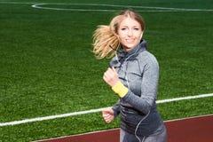 Donna con le cuffie che corre nello stadio Fotografie Stock