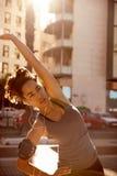 Donna con le cuffie che fanno un certo allungamento Fotografia Stock Libera da Diritti