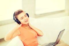 Donna con le cuffie ed il computer portatile a casa Immagine Stock Libera da Diritti