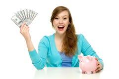 Donna con le fatture del dollaro e del piggybank Fotografia Stock