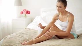 Donna con le gambe nude commoventi della piuma sul letto stock footage