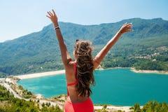 Donna con le mani su sollevate che stanno sulla cima di roccia immagine stock libera da diritti