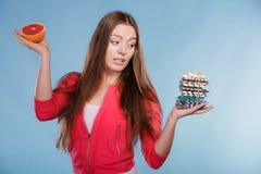 Donna con le pillole ed il pompelmo di perdita di peso di dieta fotografie stock
