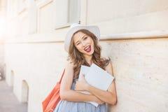 Donna con le riviste coperte in bianco che sbatte le palpebre e che mostra i pollici su Fotografia Stock Libera da Diritti