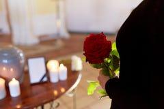 Donna con le rose e l'urna di cremazione al funerale immagini stock libere da diritti