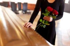 Donna con le rose rosse e la bara al funerale immagini stock