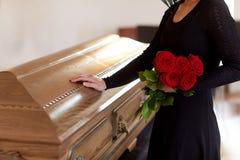 Donna con le rose rosse e la bara al funerale fotografia stock libera da diritti