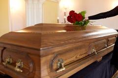 Donna con le rose rosse e la bara al funerale fotografia stock