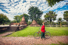 Donna con le rovine vicine della bicicletta in Tailandia immagini stock