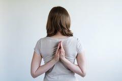 Donna con le sue mani che pongono insieme dietro lei indietro Immagini Stock Libere da Diritti