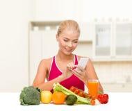 Donna con le verdure che indicano allo smartphone immagini stock libere da diritti