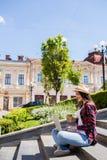 Donna con limonade che si siede sulle scale della città e che per mezzo del computer portatile Fotografie Stock Libere da Diritti