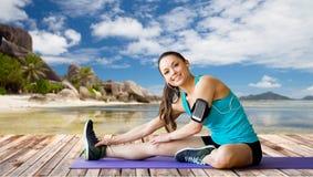 Donna con lo smartphone che allunga gamba sulla stuoia Immagini Stock