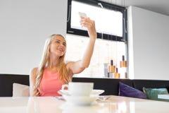 Donna con lo smartphone che prende selfie al ristorante fotografia stock libera da diritti