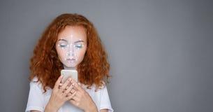 Donna con lo smartphone facendo uso del sistema di riconoscimento di identificazione del fronte immagine stock