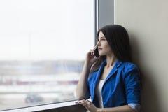 Donna con lo smartphone nell'ingresso dell'ufficio fotografie stock libere da diritti